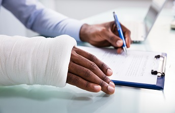 Man with cast on right arm filling out an insurance claim with left hand